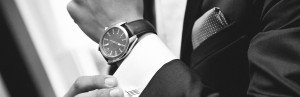 Close up of elegant man in suit with watch on hand